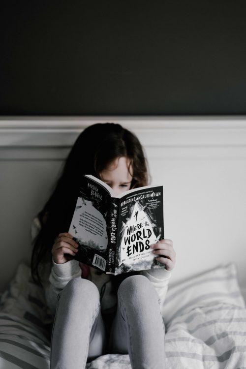 Une petite fille en train de lire un livre