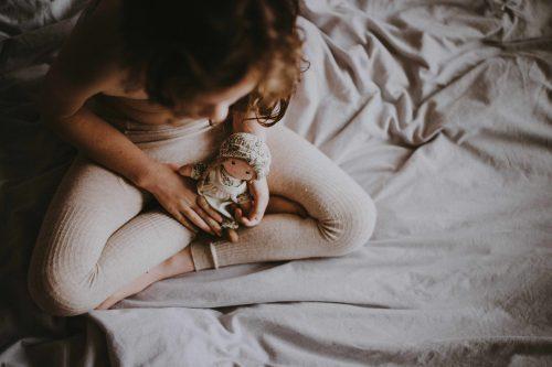Une petite fille dans un lit avec une poupée